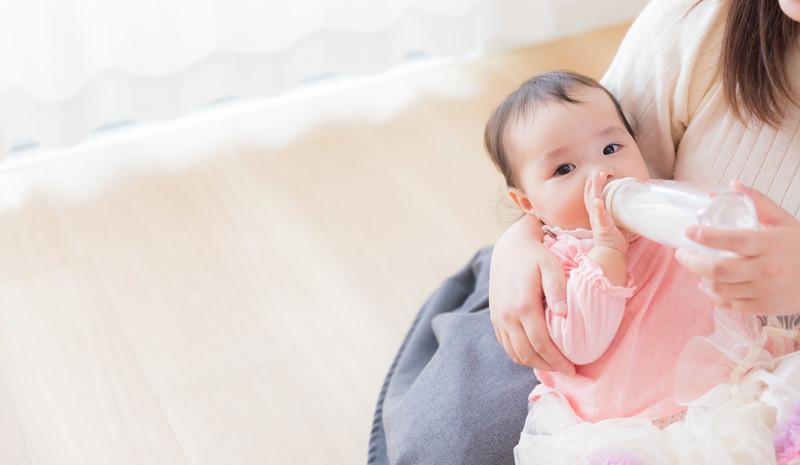 ママに抱かれて哺乳瓶でミルクを飲む赤ちゃんのフリー画像